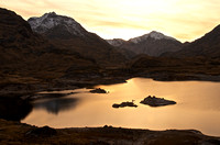 Sun sets over Ben Aden and Luinne Bheinn.